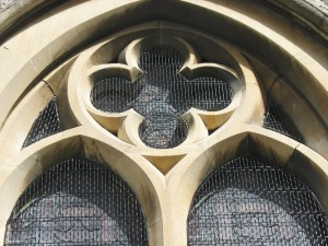 Close up view of the traditional window guards shows the quatrefoil tracery and insets