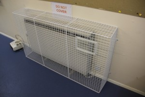 One of the bespoke heater guards AIANO manufactured for Dollis Junior School with 'do not cover' sign displayed above